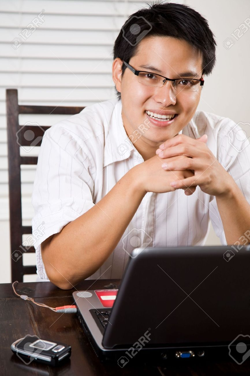 3705527-An-asian-entrepreneur-working-on-his-laptop-from-home-Stock-Photo