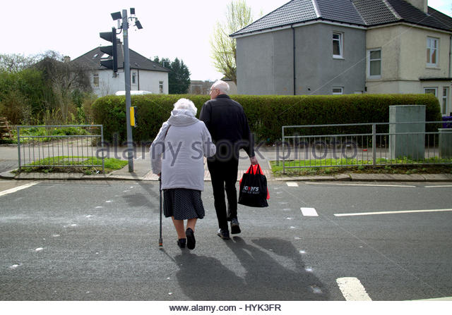 old-couple-crossing-road-at-traffic-lights-with-walking-stick-hyk3fr